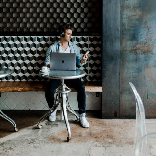 Man in cafe on laptop and phone