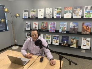 CEO and podcast host Adam Stoker smiles in a conference room with podcast recording materials including a laptop, headphones and microphone.
